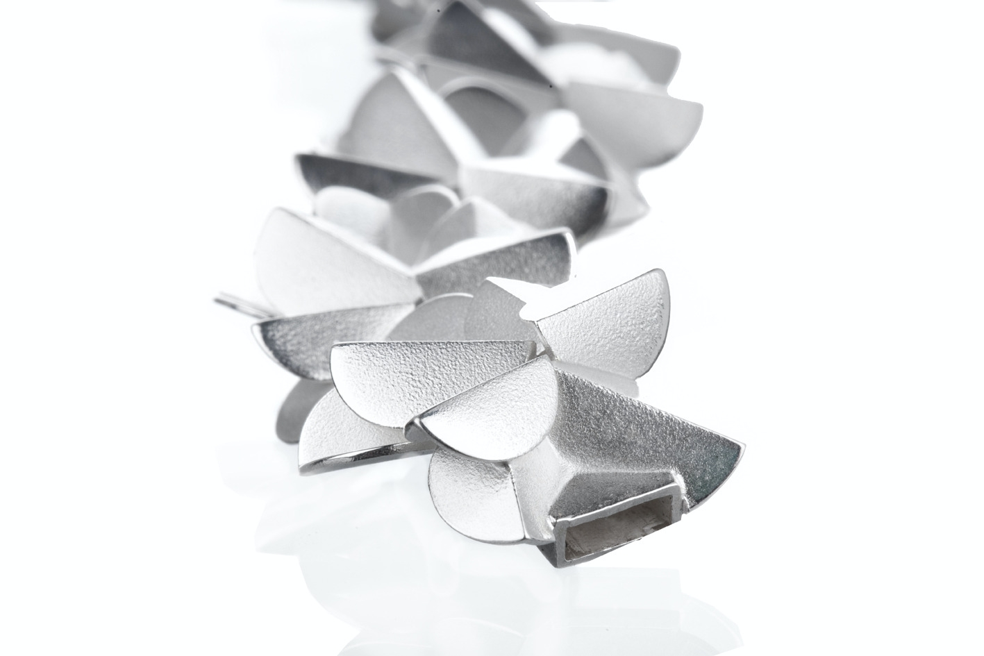 karakoram architectural earing with folding silver designs overlapping eachother. design by jewellery designer Kaja Gjedebo